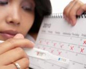 девушка держит возле календаря тест на беременность